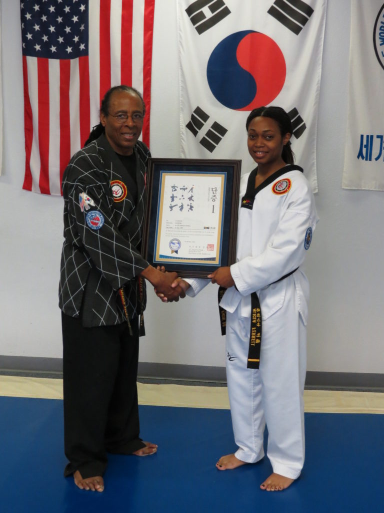 Master Bell shaking hands with student while holding award